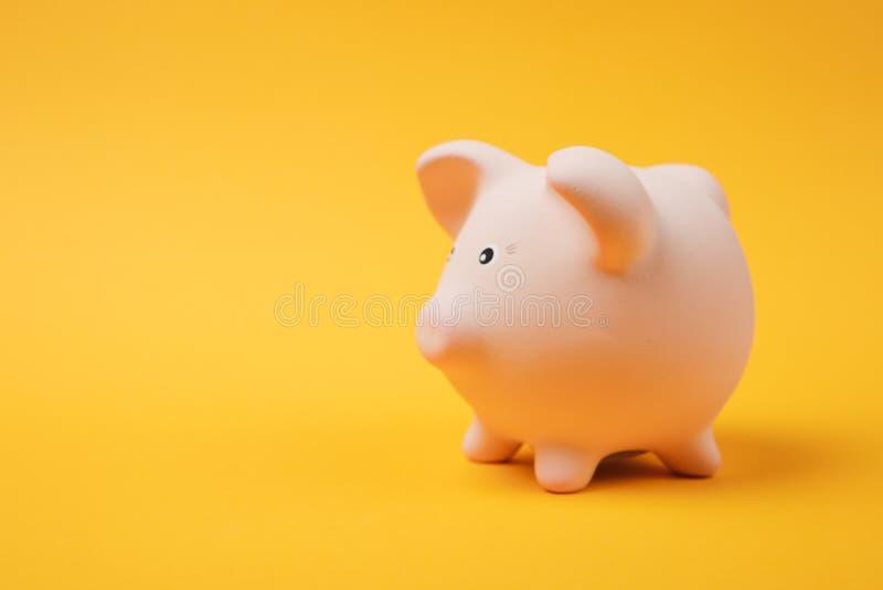 Fim acima da foto, vista lateral do banco leitão cor-de-rosa do dinheiro no fundo amarelo brilhante da parede Acumulação do dinhe imagens de stock