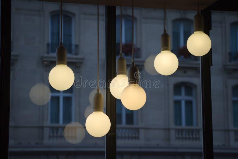 Fim acima da lâmpada leve morna do teto com reflexão na janela na cafetaria na noite, nivelando no café de Paris fotos de stock royalty free