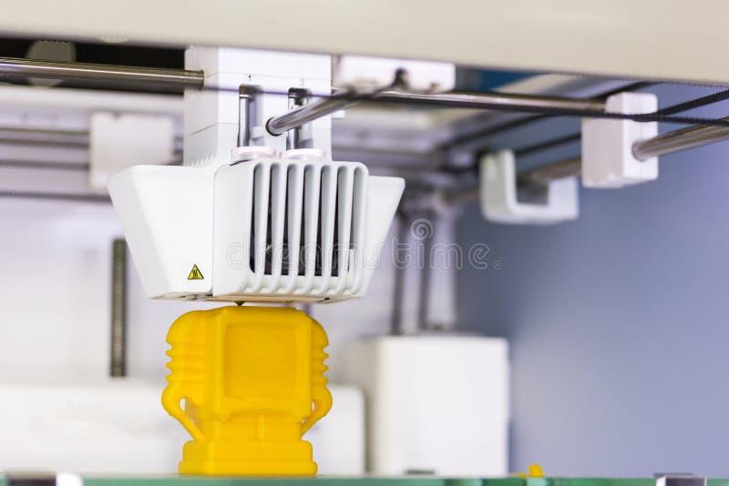 Fim acima da máquina tridimensional da impressora 3d que trabalha o modelo plástico do brinquedo na fábrica imagens de stock royalty free