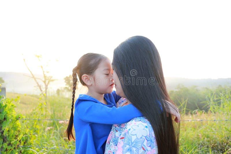 Fim acima da mãe asiática e das filhas que beijam no campo do prado na manhã foto de stock