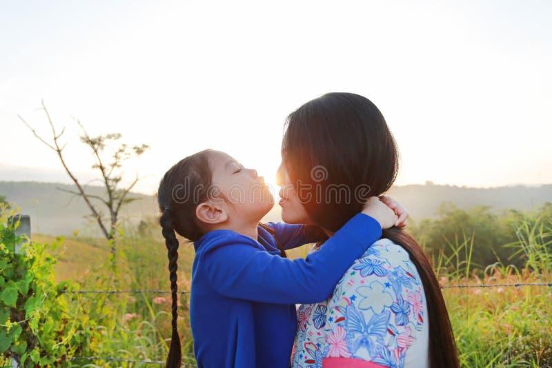 Fim acima da mãe asiática e das filhas que beijam no campo do prado no nascer do sol da manhã imagem de stock
