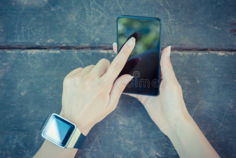 Fim acima da mão fêmea que guarda o telefone esperto e que veste o relógio foto de stock royalty free