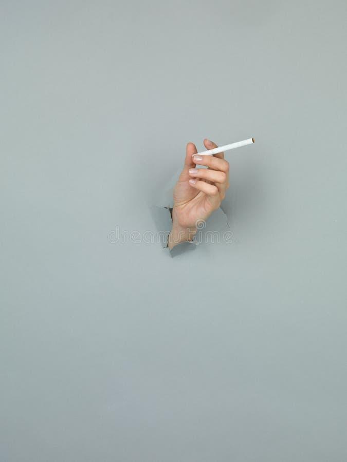 Mão fêmea que guardara o cigarro imagens de stock