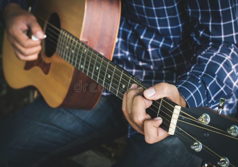Fim acima da mão masculina que joga a guitarra imagem de stock