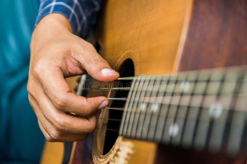 Fim acima da mão masculina que joga a guitarra imagem de stock royalty free