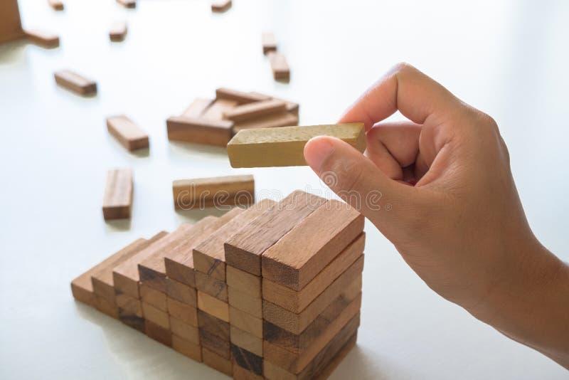 Fim acima da mão que guarda o jogo de madeira dos blocos Mananement do risco imagens de stock royalty free
