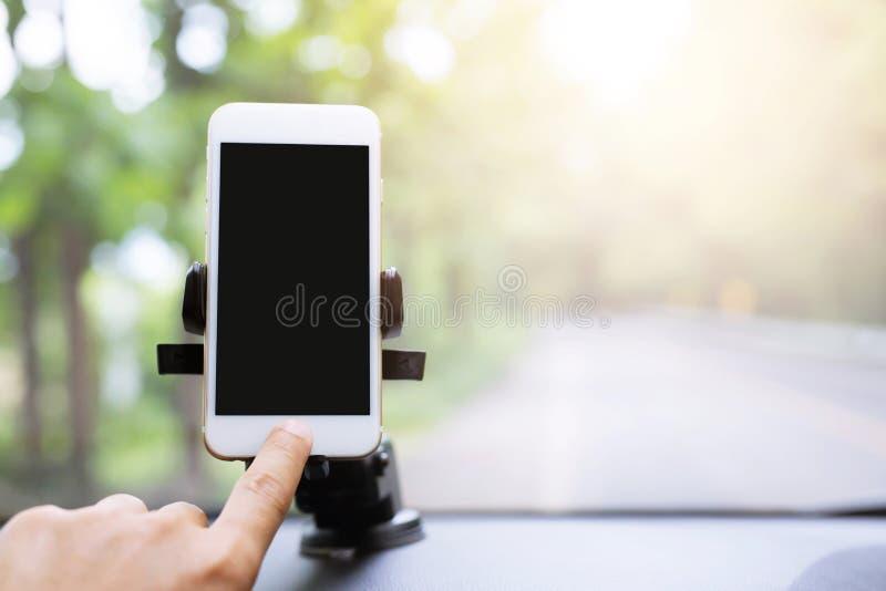 Fim acima da mão que guarda usando o telefone esperto móvel com a tela preta na vara do suporte do para-brisa dianteiro do consol fotos de stock