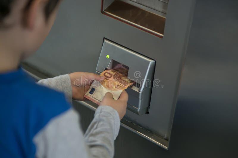Fim acima da mão que introduz a cédula na máquina, tique de compra foto de stock royalty free