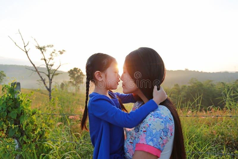 Fim acima da m?e asi?tica e das filhas que beijam no campo do prado no nascer do sol da manh? imagens de stock