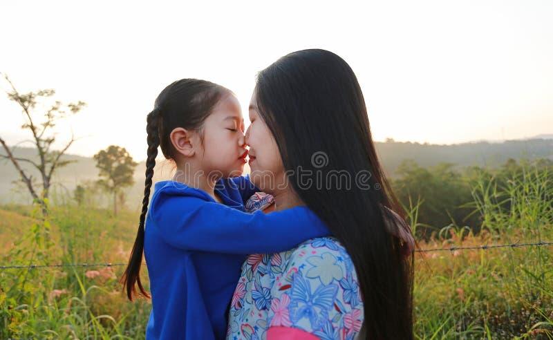Fim acima da m?e asi?tica e das filhas que beijam no campo do prado no nascer do sol da manh? imagem de stock royalty free