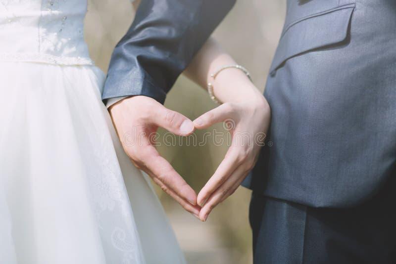 Fim acima da m?o e da noiva do noivo O homem novo e os pares fêmeas casam-se imagens de stock