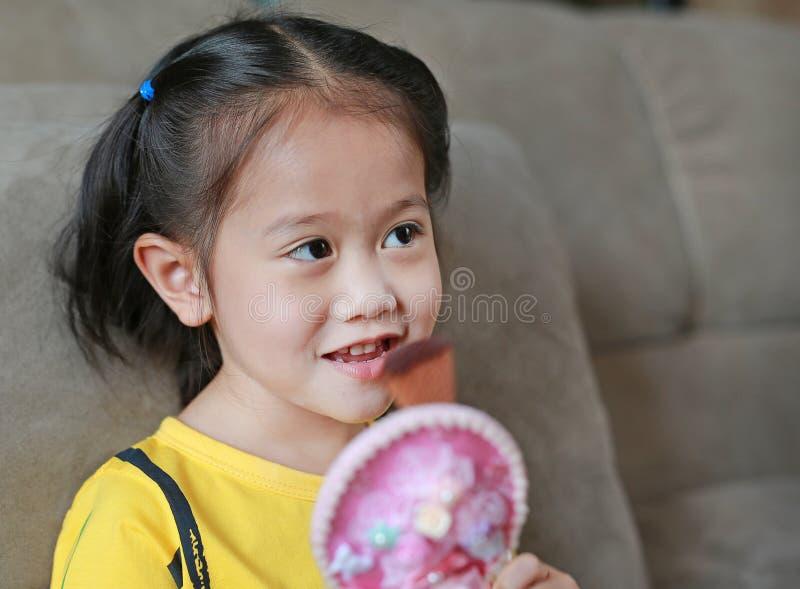 Fim acima da menina asiática da criança que faz a composição fotos de stock