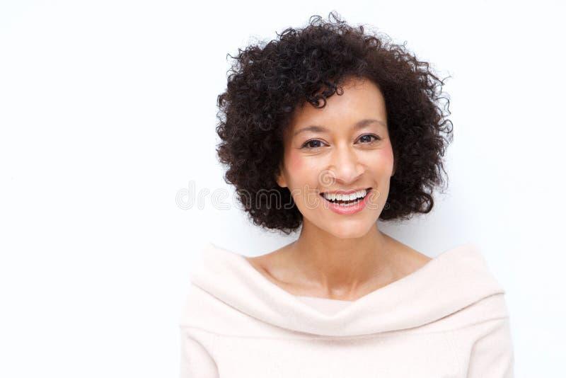 Fim acima da mulher afro-americano da Idade Média atrativa que sorri contra o fundo branco fotografia de stock
