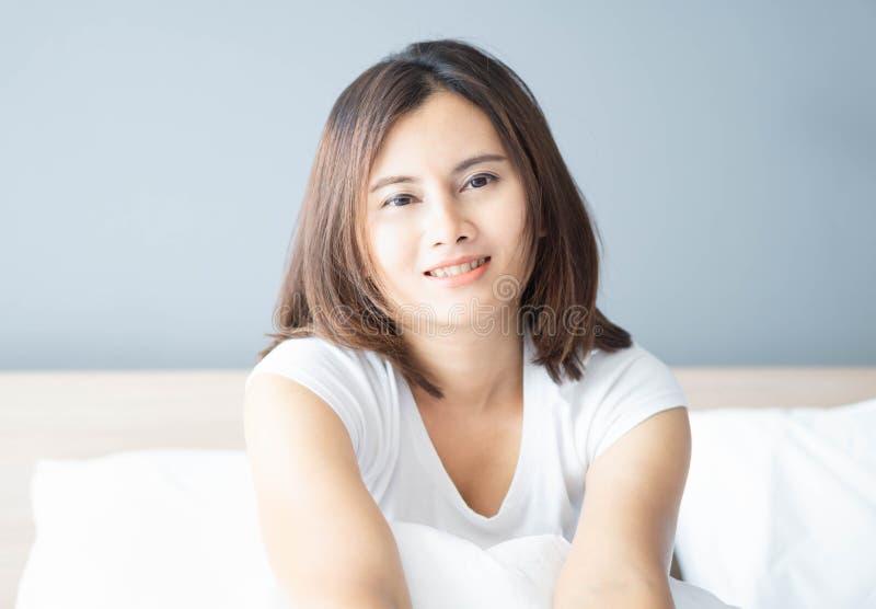 Fim acima da mulher asiática que sorri com a cara feliz que encontra-se na cama branca na manhã, foco seletivo imagens de stock