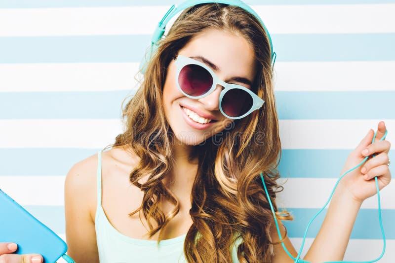Fim acima da mulher atrativa nova do retrato à moda do verão com cabelo encaracolado longo em óculos de sol azuis que escuta a mú foto de stock royalty free