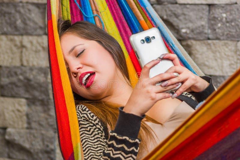 Fim acima da mulher bonita nova que dorme em uma rede com sua boca aberta, quando for com um telefone celular em suas mãos fotos de stock royalty free
