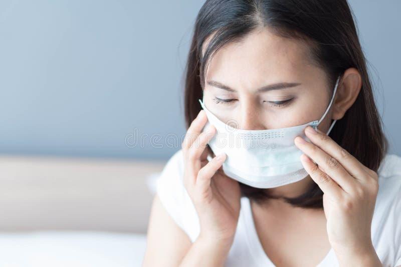 Fim acima da mulher doente que veste a cara médica da máscara que encontra-se na cama branca, nos cuidados médicos e no conceito imagem de stock royalty free