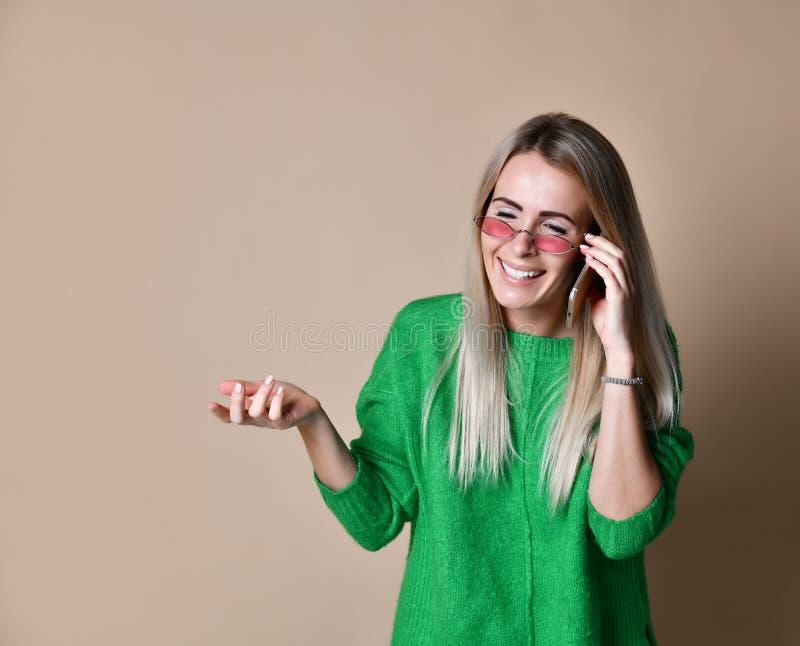 Fim acima da mulher loura nova que fala a alguém em seu telefone celular ao olhar na distância com expressão facial feliz fotos de stock royalty free