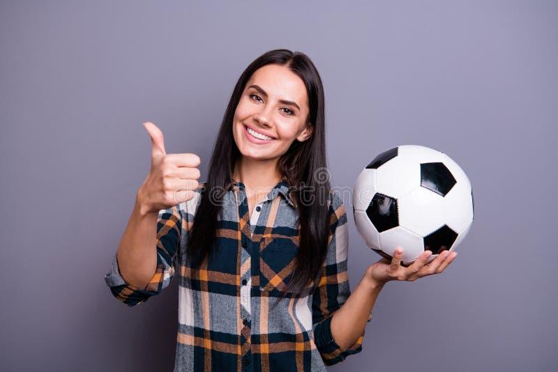 Fim acima da surpresa da foto bonita ela sua senhora para manter o polegar do braço de mão aumentado acima da bola de futebol do  imagem de stock royalty free
