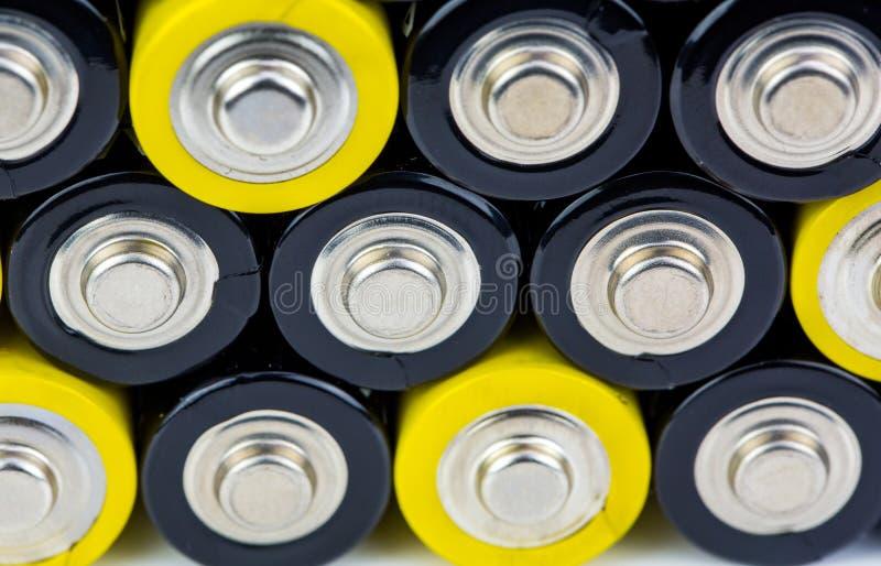 Fim acima das fileiras coloridas da seleção do fundo abstrato da energia das baterias do AA de baterias coloridas imagem de stock