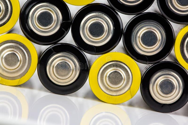 Fim acima das fileiras coloridas da seleção do fundo abstrato da energia das baterias do AA de baterias coloridas fotografia de stock