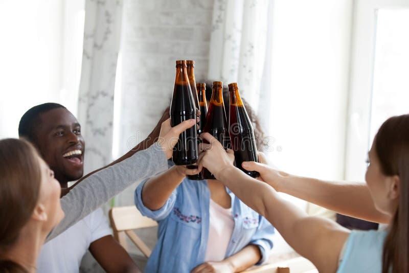 Fim acima das garrafas felizes do tinido dos povos da raça misturada com cerveja foto de stock royalty free