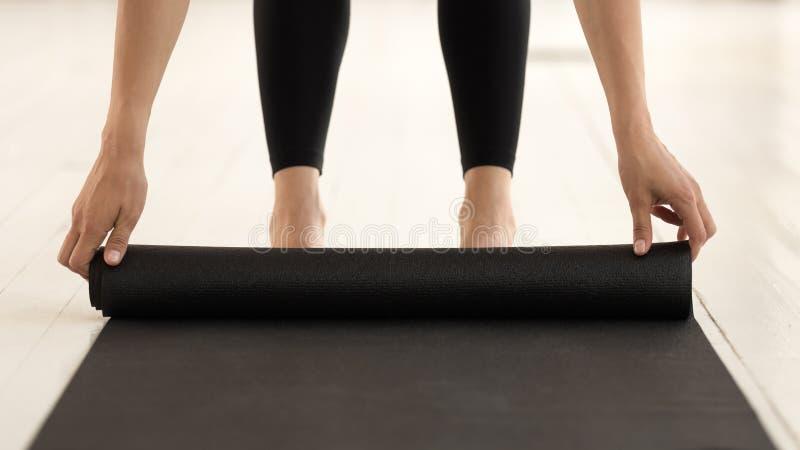 Fim acima das mãos da mulher da vista que rolam a esteira após a prática da ioga imagem de stock royalty free