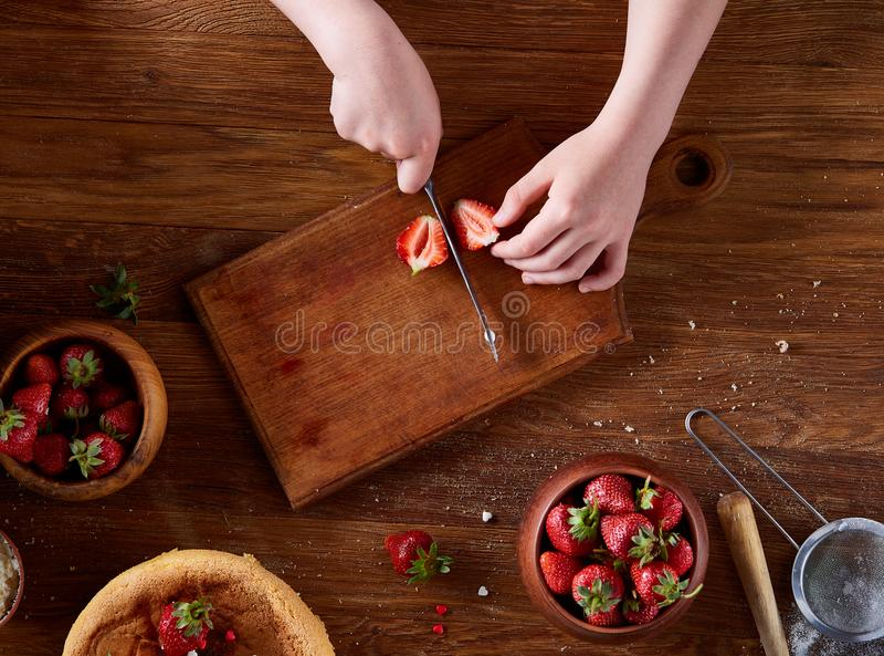 Fim acima das mãos do ` s da menina que adicionam o creme sobre o bolo delicioso da morango, fim acima, foco seletivo fotografia de stock royalty free
