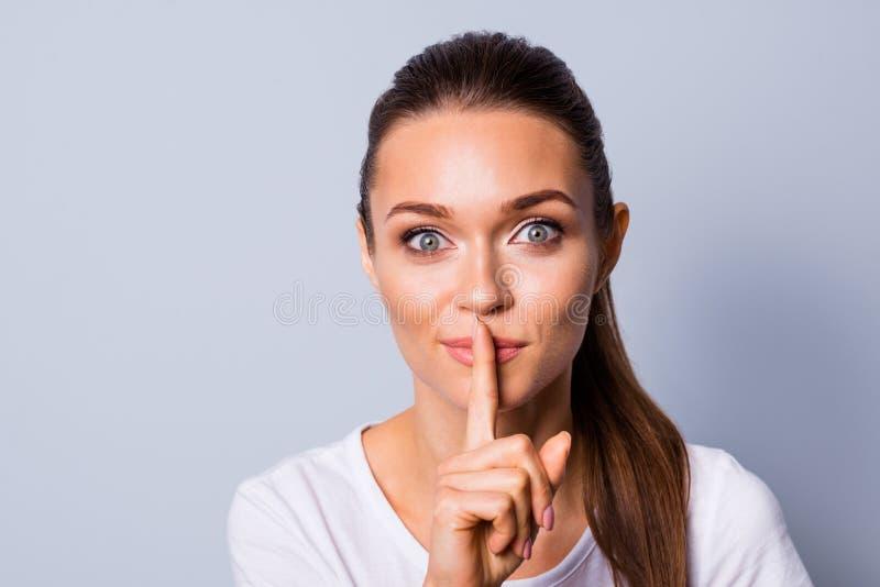 Fim acima de surpreendente bonito da foto ela sua parada secreta da boca dos bordos do dedo do sil?ncio da informa??o da apar?nci foto de stock