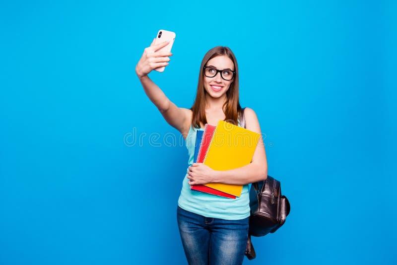 Fim acima de surpreendente bonito da foto seu estudo da posse da senhora aplica o braço de mão traseiro do telefone do saco para  fotografia de stock royalty free