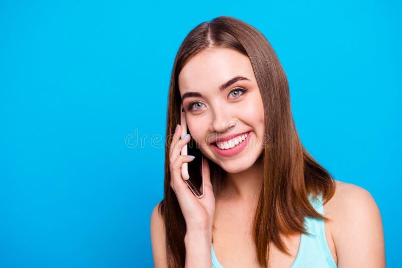 Fim acima de surpreendente bonito da foto seus braços de mãos toothy da posse da senhora telefona o lado que esperto do olhar do  foto de stock