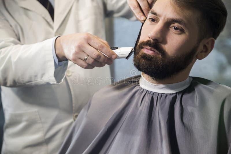 Fim acima de um homem que tem seu corte do cabelo imagens de stock royalty free