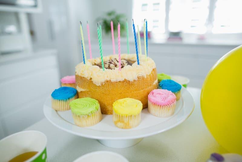 Fim acima do bolo de aniversário no suporte com bolo e velas do copo foto de stock royalty free