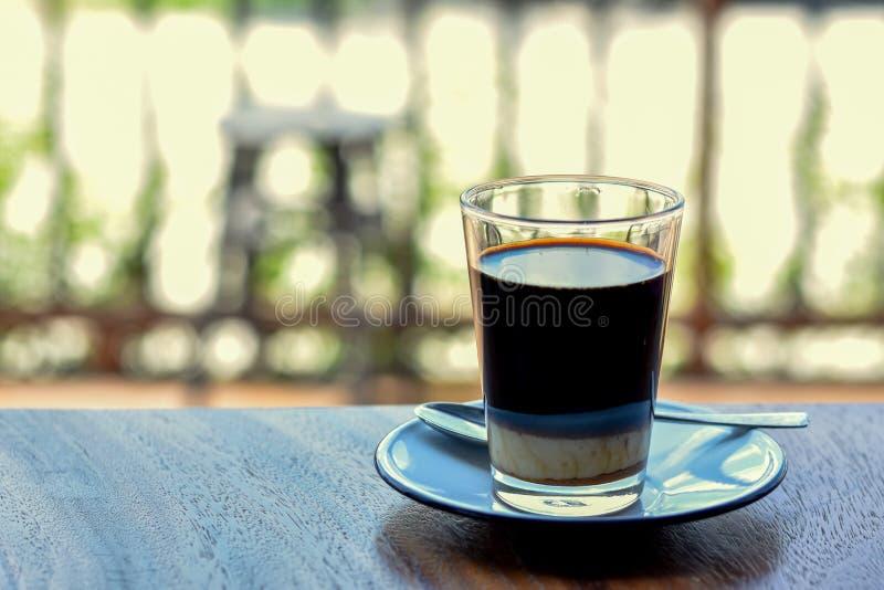 Fim acima do café da vista em um vidro na tabela de madeira com fundo borrado fotografia de stock