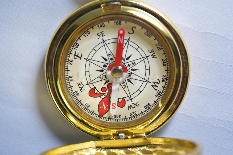 Fim acima do compasso dourado magn?tico isolado no fundo branco imagens de stock