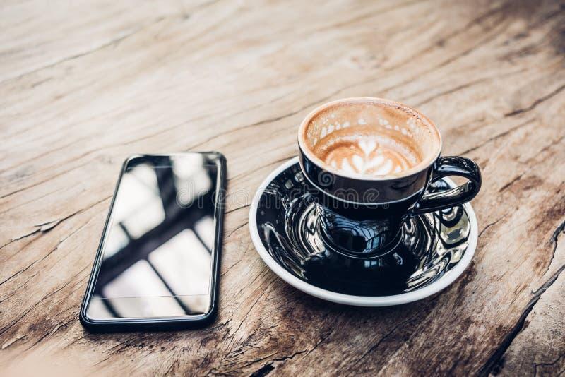 Fim acima do copo e do móbil de café preto quente na tabela de madeira perto da janela com luz solar no restaurante do café Estil imagem de stock