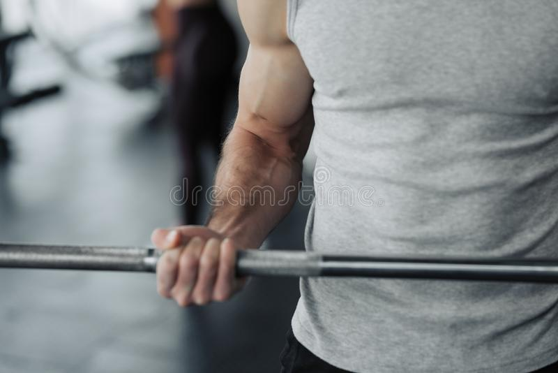 Fim acima do dumbell do recolhimento do homem no gym o exercício com dá certo o programa para saudável imagens de stock royalty free