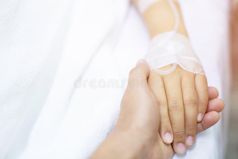 Fim acima do foco dos povos na mão do mal doente paciente na cama fotos de stock