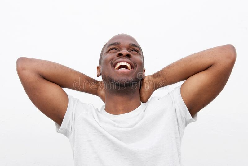 Fim acima do homem afro-americano despreocupado que ri com mãos atrás da cabeça contra o fundo branco imagem de stock