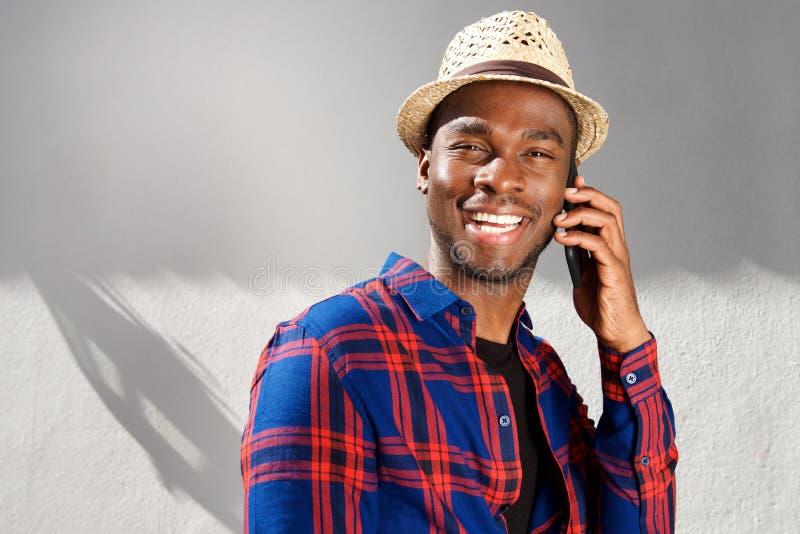 Fim acima do homem afro-americano feliz com chapéu que fala com o telefone celular pela parede branca fotos de stock