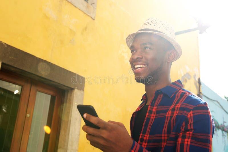 Fim acima do homem afro-americano feliz com telefone celular fora imagens de stock royalty free