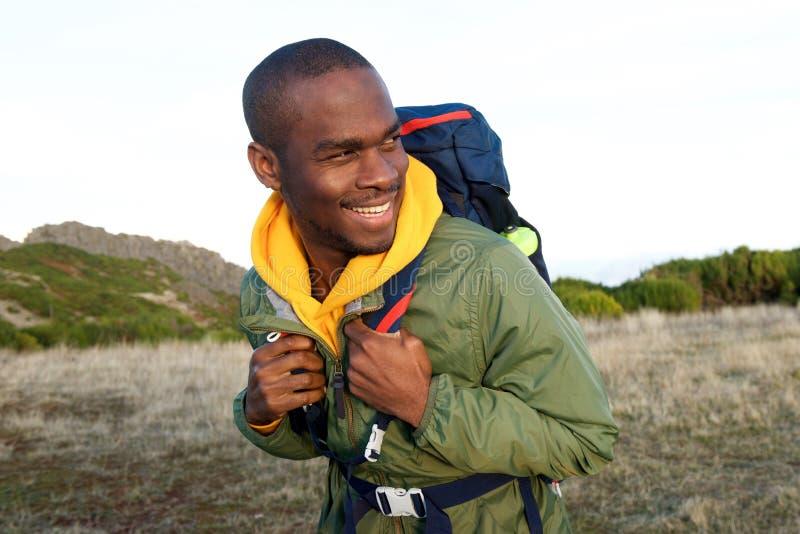 Fim acima do homem afro-americano feliz que caminha com a trouxa na natureza fotos de stock