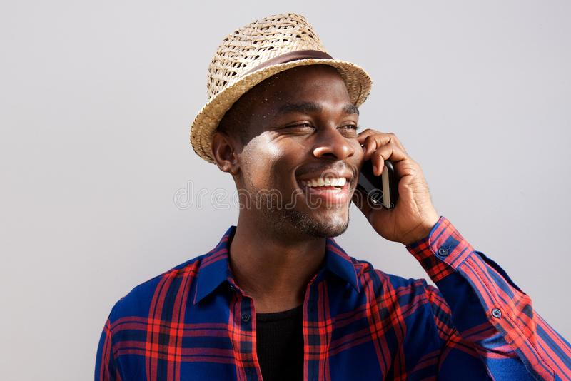 Fim acima do homem afro-americano feliz que fala com o telefone celular contra a parede branca foto de stock royalty free