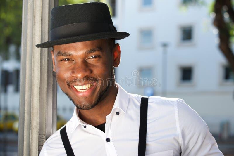 Fim acima do homem afro-americano novo à moda que sorri com suspensórios e chapéu fotografia de stock royalty free