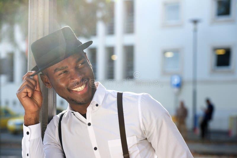 Fim acima do homem afro-americano novo considerável com suspensórios e chapéu que sorri na cidade imagens de stock