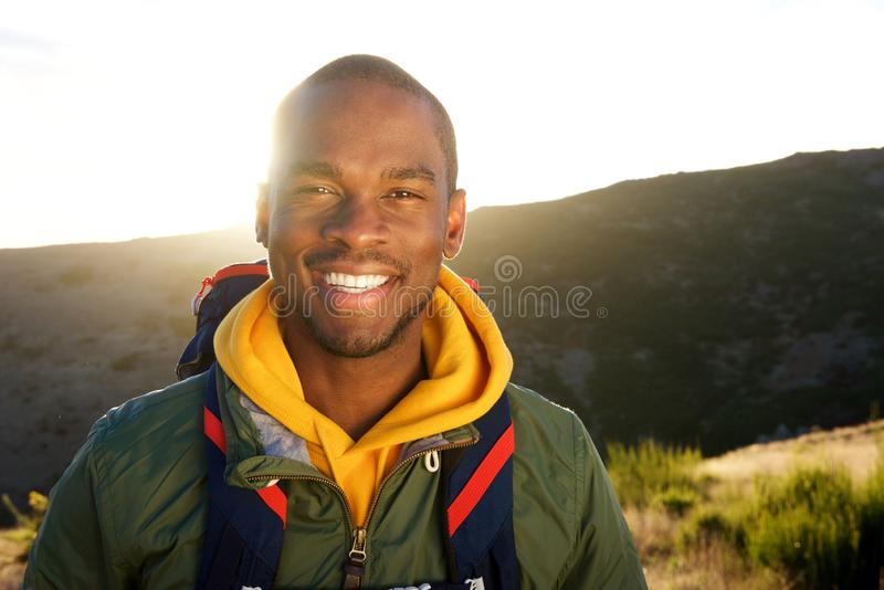 Fim acima do homem afro-americano novo considerável com a trouxa que levanta na natureza com por do sol no fundo imagem de stock royalty free