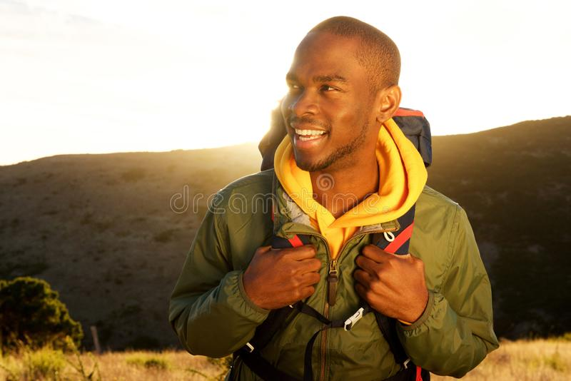 Fim acima do homem afro-americano novo considerável com trouxa que sorri com nascer do sol no fundo fotografia de stock royalty free