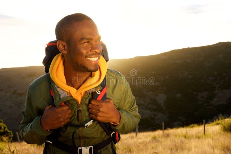 Fim acima do homem afro-americano novo considerável com trouxa que sorri com por do sol no fundo fotos de stock royalty free