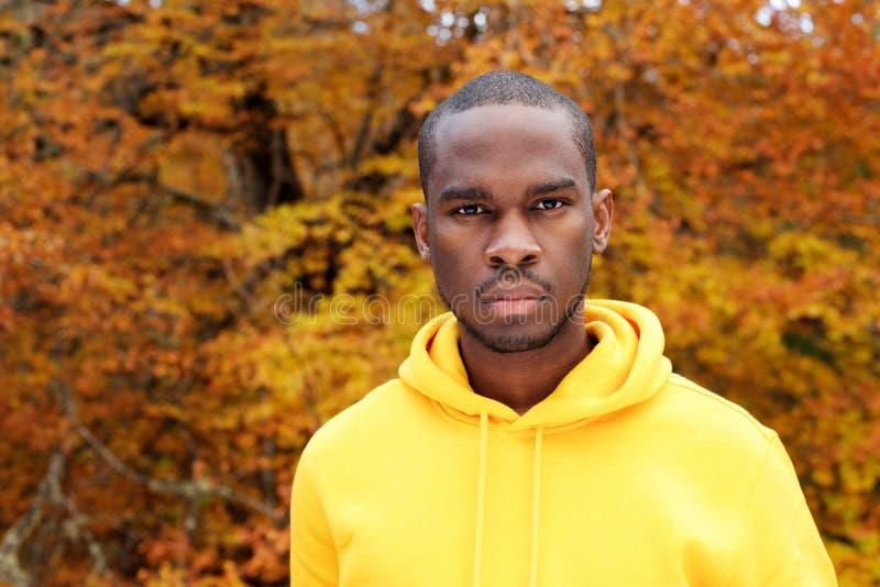 Fim acima do homem afro-americano novo considerável contra as folhas de outono no fundo foto de stock royalty free
