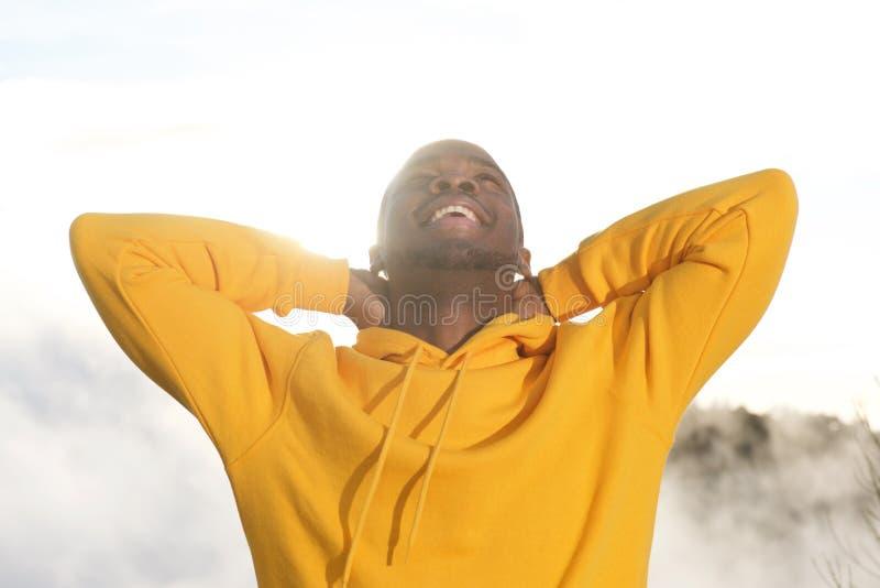 Fim acima do homem afro-americano novo considerável que sorri com mãos atrás da cabeça e do sol no fundo foto de stock royalty free